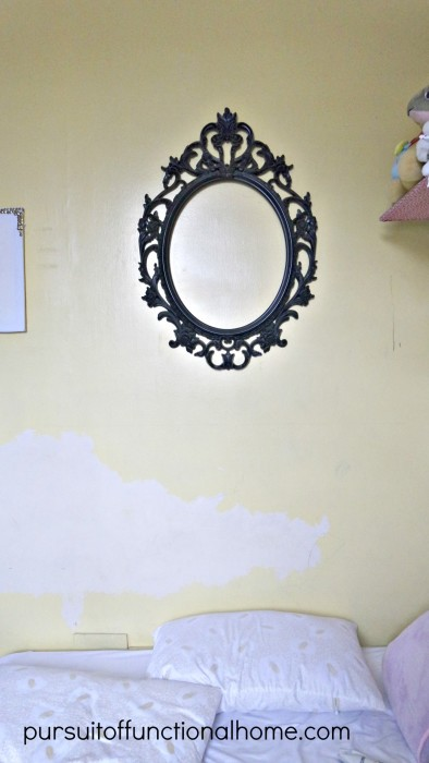 Yellow wall with chipped paint with victorian mirror black